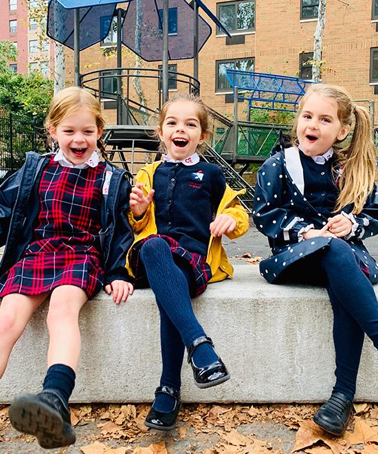 Three Geneva School students smiling on playground outside