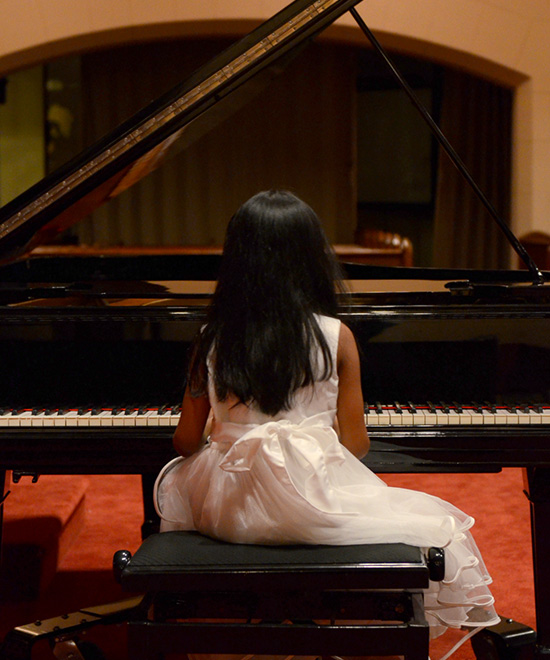 Young girl playing piano on stage