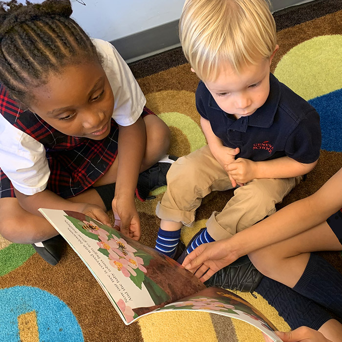 Geneva School student reading to younger student