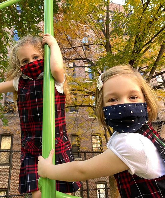 Two Geneva School girls wearing masks playing outside on playground