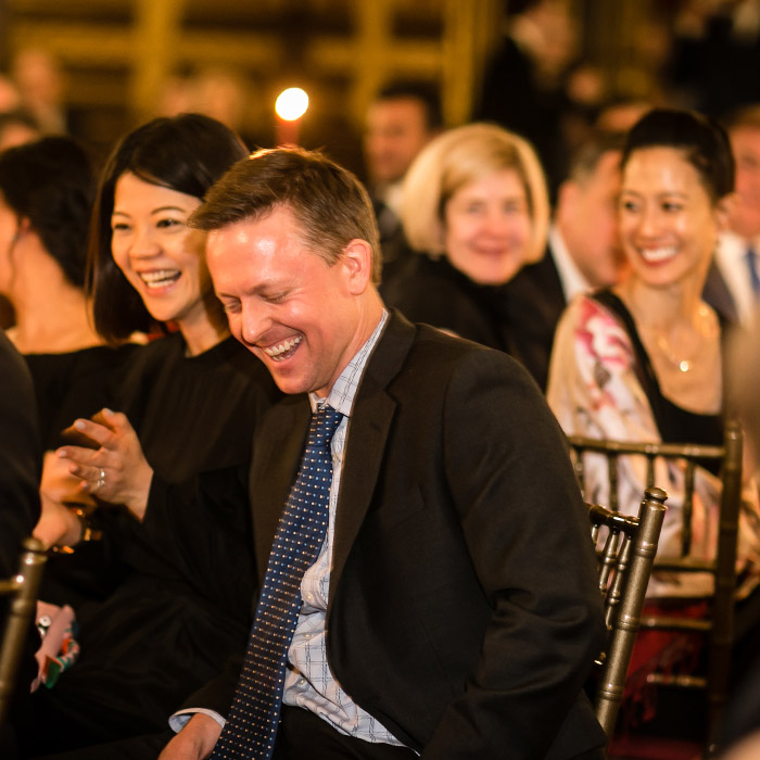Man in suit laughing with other adults
