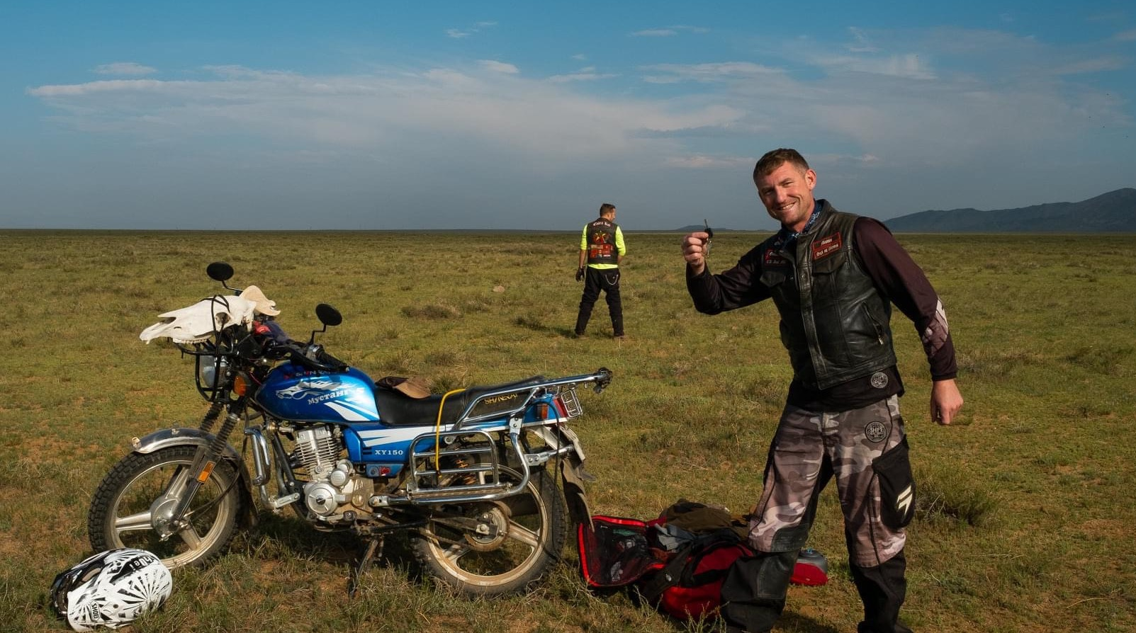 Josh Melick and Travis Pollock and a motorcycle on the Mongolia Steppe grasslands
