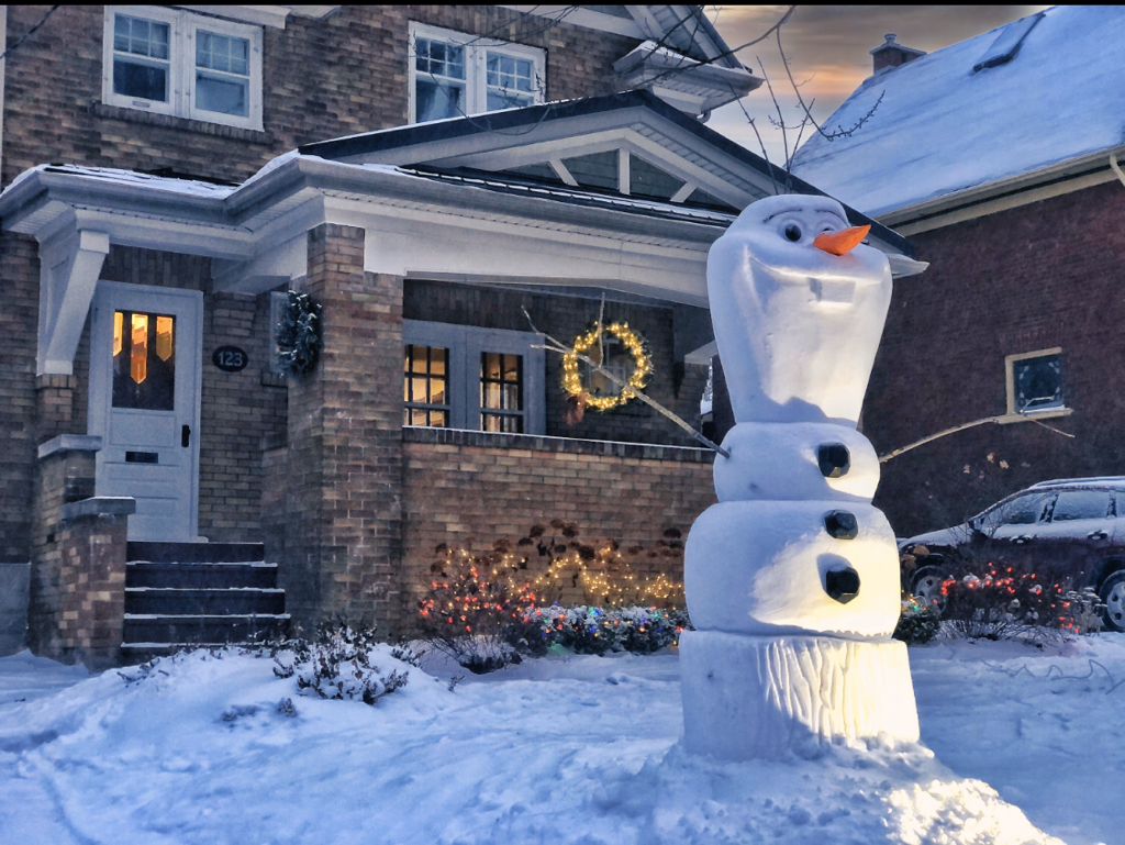 Image of a large snow sculpture of Olaf the snowman from the Disney movie Frozen in front of a brown brick house in winter.i