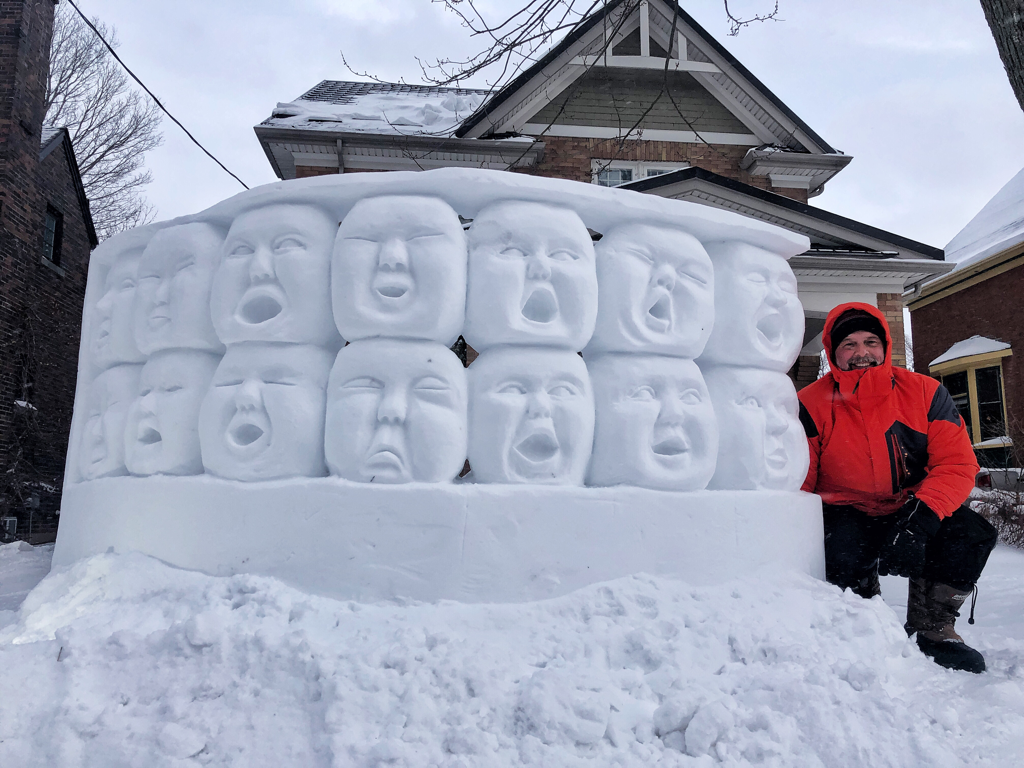 Image of Matt Morris (snow sculptuor) standing next to a snow sculpture in front of his house. Sculpture is two rows of heads stacked and making different facial expressions.