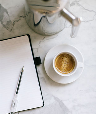 Notebook, mug and coffee on a table