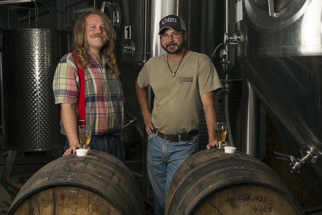 Two men standing at a distillery.