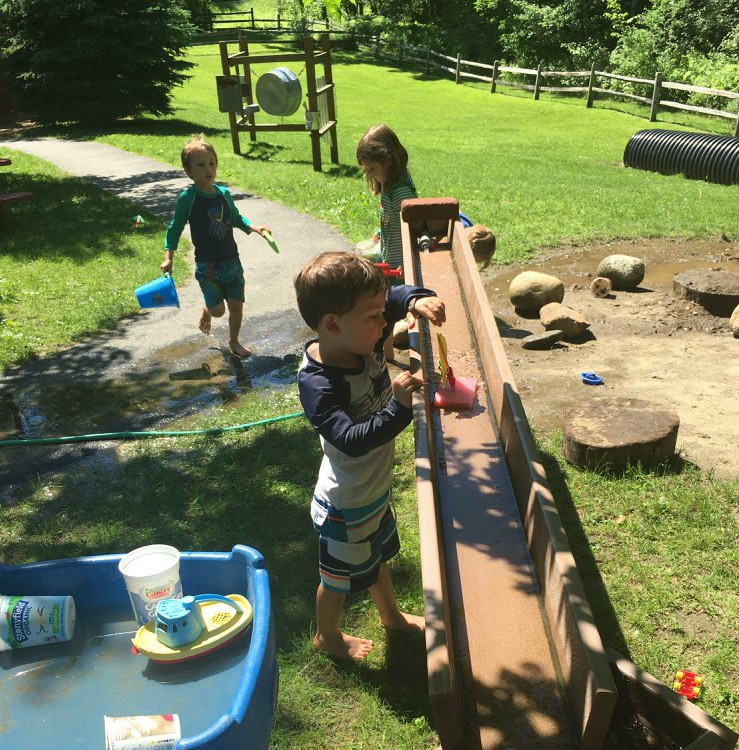 Preschool children playing wih toy boats in wooden water slide