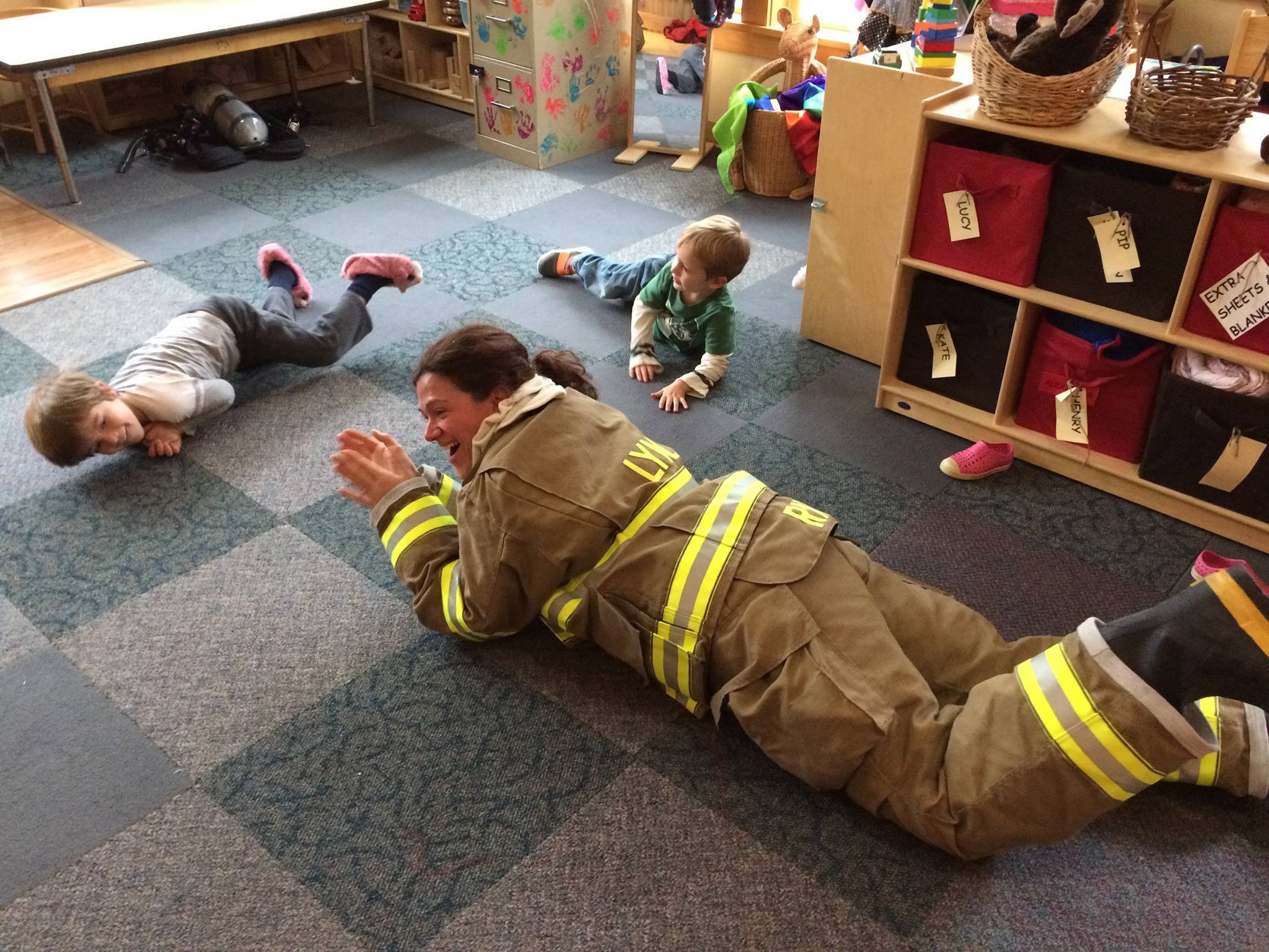 firefighter rolling on floor with preschool children