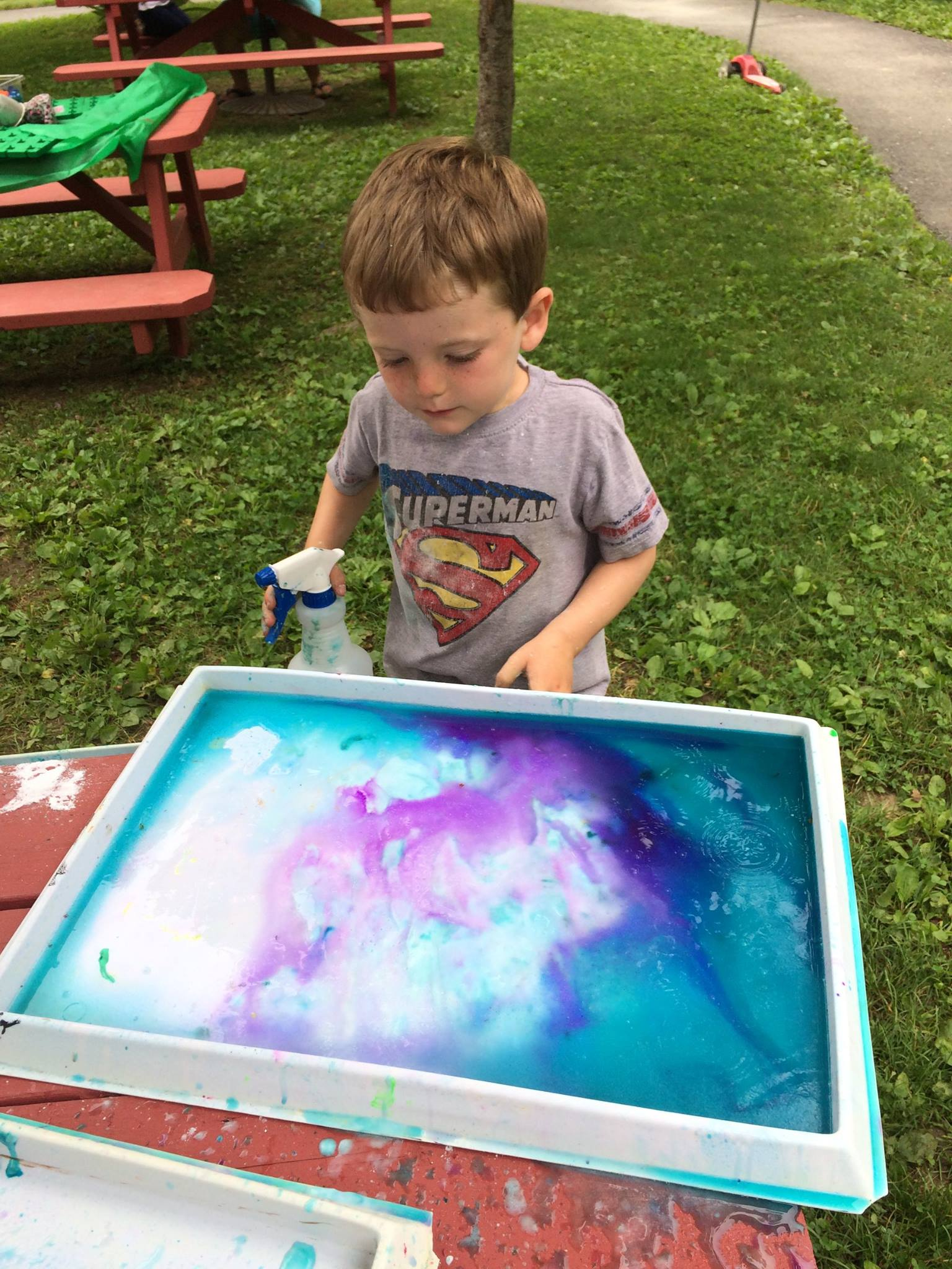 preschool child creating art with water and paint