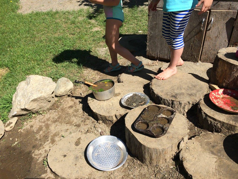 preschool children making mudpies outdoors