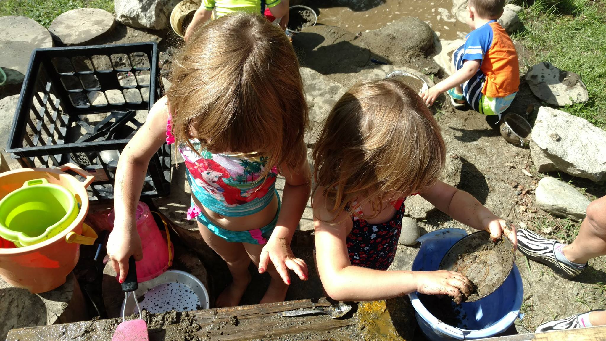 Preschool children playing with mud outside