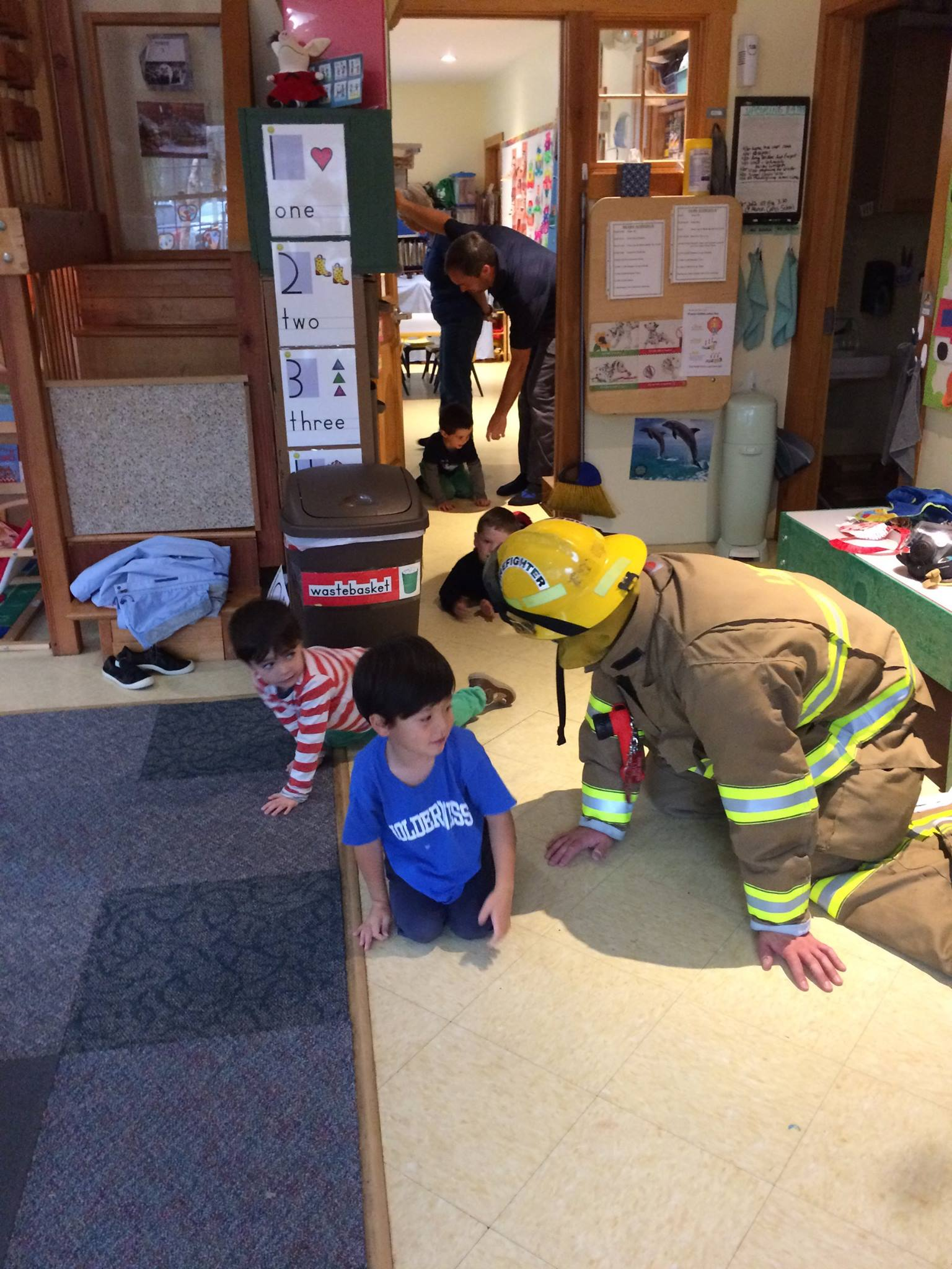 firefighter teaching preschool children while crawling on floor