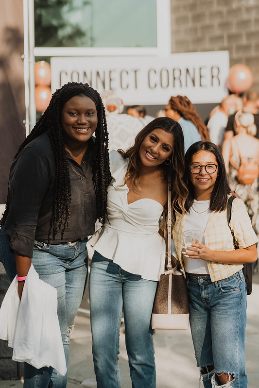 Three young women smiling at a women's event for a non-denominational church in omaha nebraska