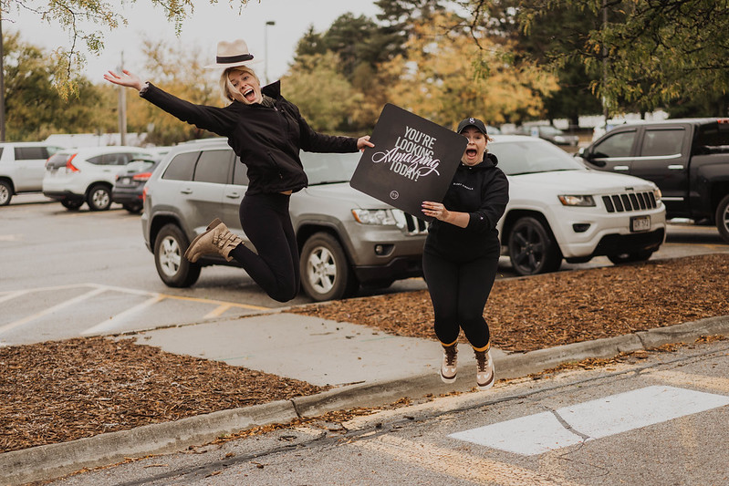 "two women smiling and jumping in the air while holding a sign that says, ""you're looking amazing today!"" in the parking lot of a christian church in omaha nebraska"