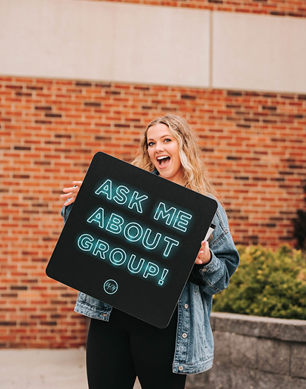 "Woman holding a sign that says ""Ask me about group!"" at a christian women's event for a non-denominational church in omaha nebraska"
