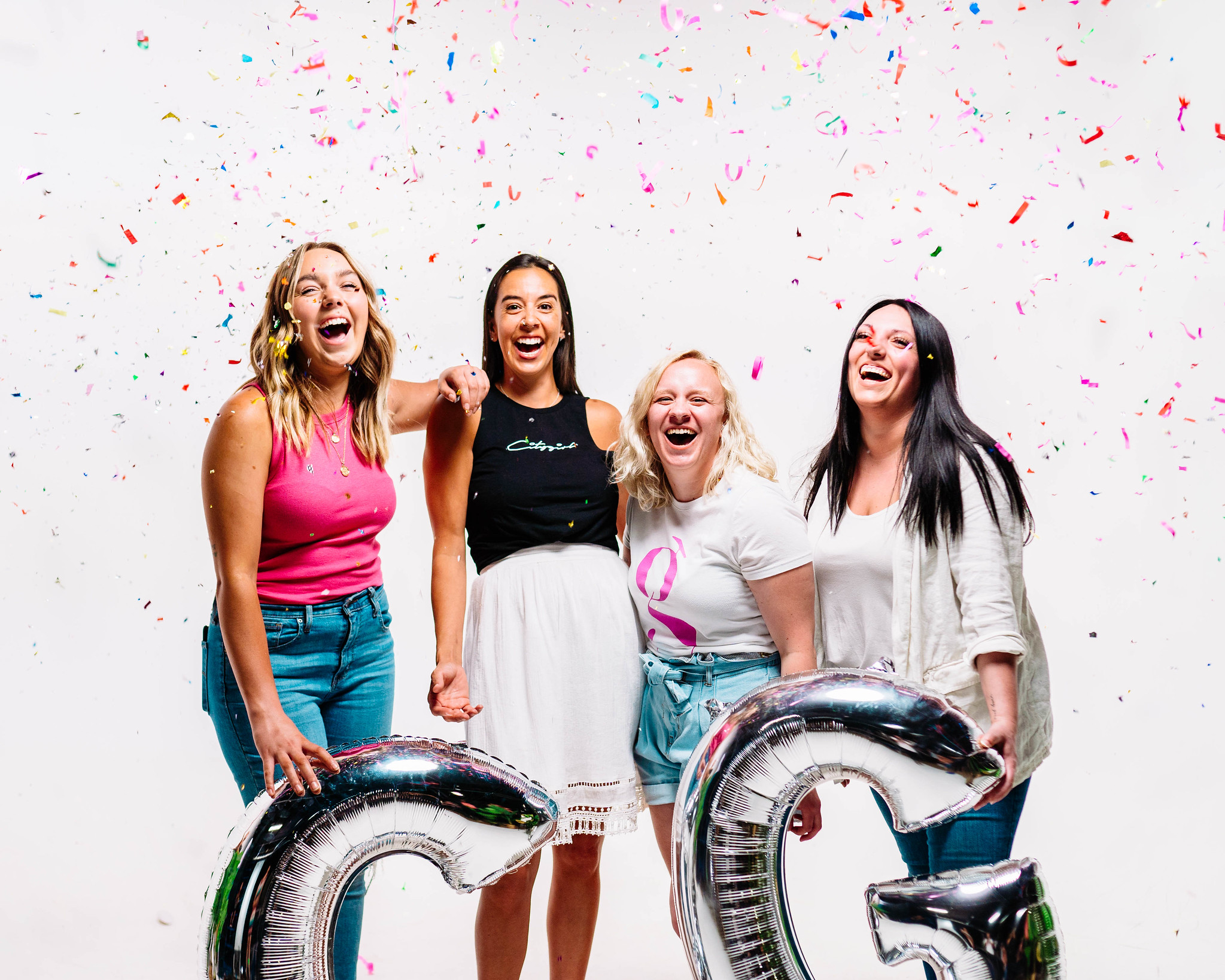 women smiling at laughing as confetti falls from the ceiling while they are holding large silver balloons at a women's event for a christian church in omaha nebraska