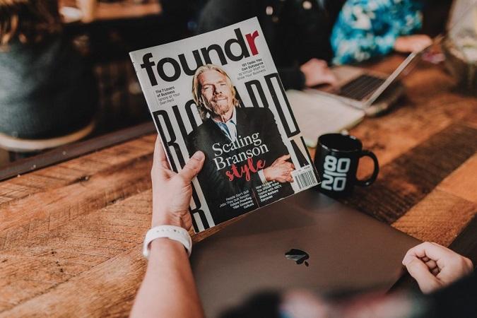 scaling branson style magazine, laptop and magazine on table
