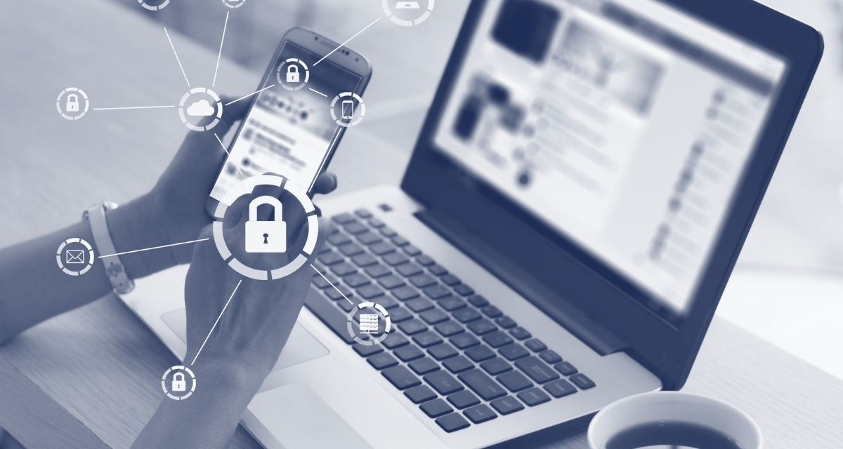 holding a phone over laptop cybersecurity