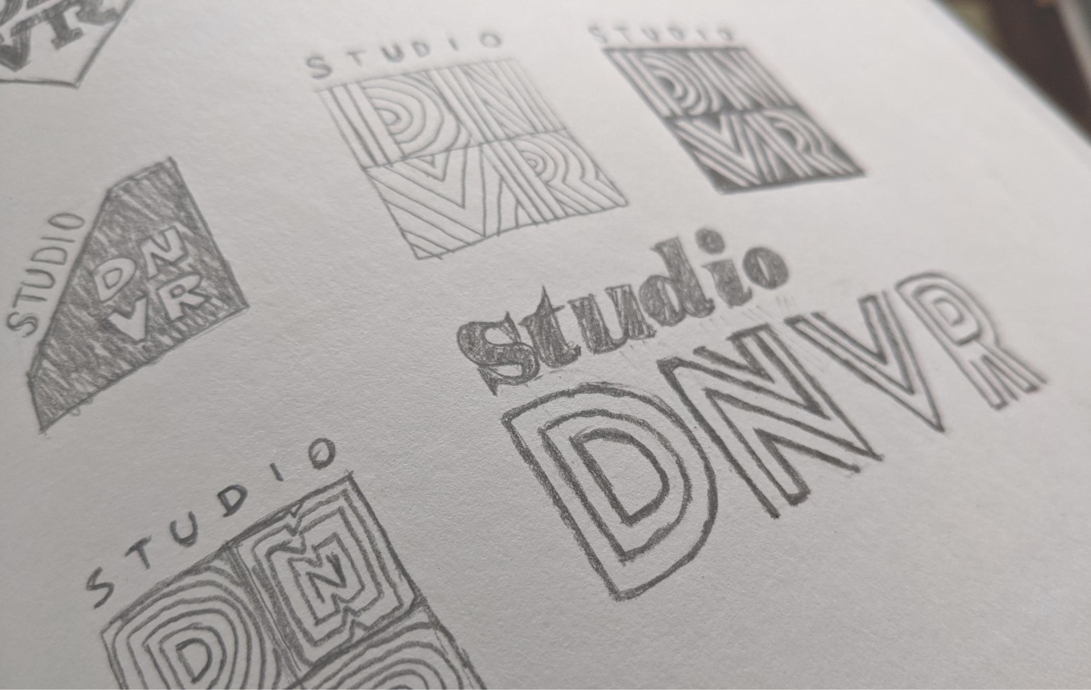 Sketches in a notebook of Studio DNVR logo concepts