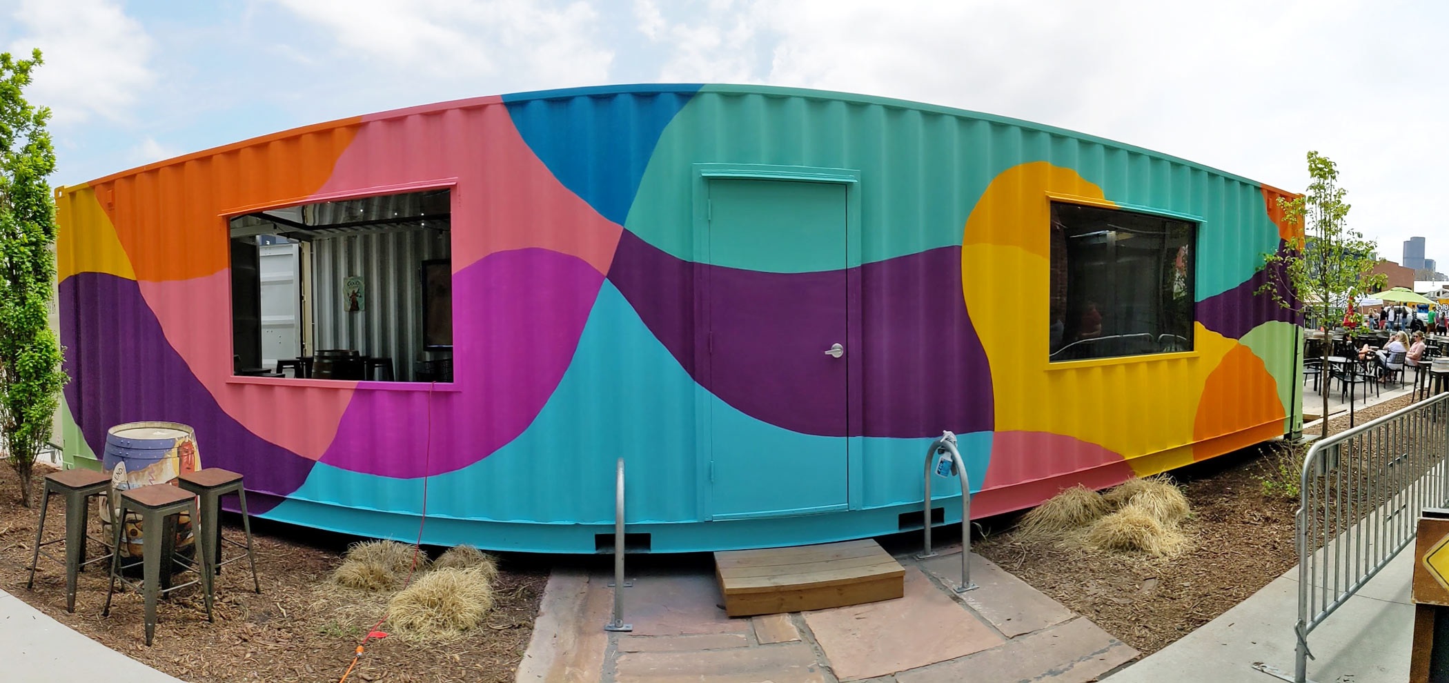 An abstract mural depicting colorful blobs painted on a shipping container in front of Odell Brewing Company, Denver, Colorado