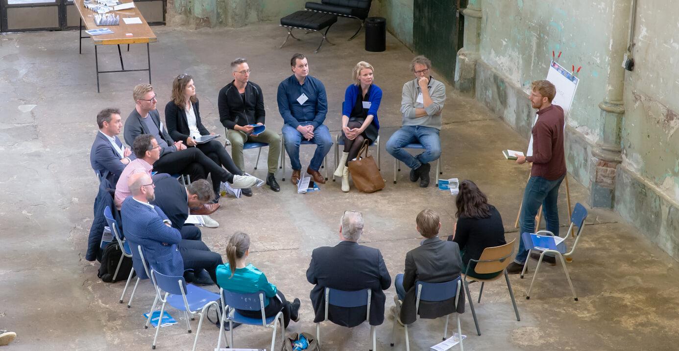 In een creatieve sessie zitten deelnemers klaar voor hun volgende opdracht