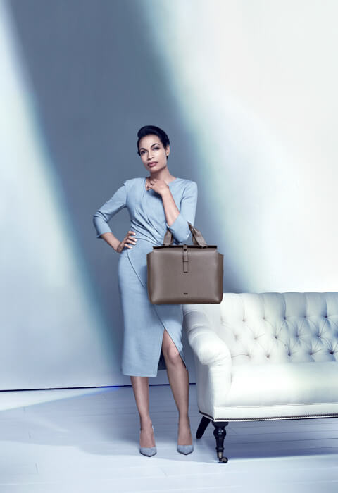 A portrait of Rosario Dawson dressed formally as a businesswoman