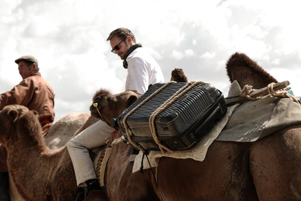 A Tumi bag tied onto a camel