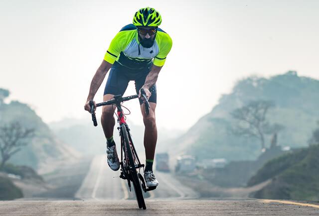 A man on a bike wearing a bright yellow jersey