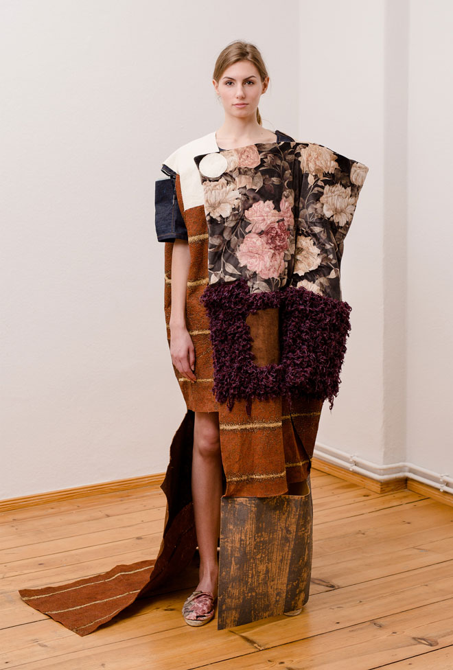 Textile art object on female consisting of a patchwork on fabrics made of bark, knit, quilted velvet and printed cork - front view