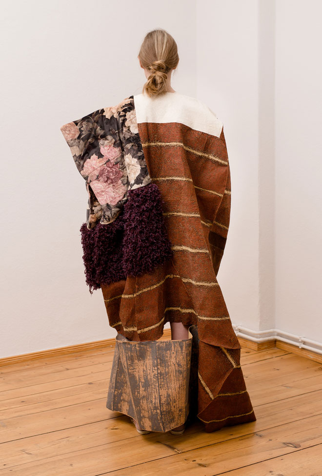 Textile art object on female consisting of a patchwork on fabrics made of bark, knit, quilted velvet and printed cork - back view