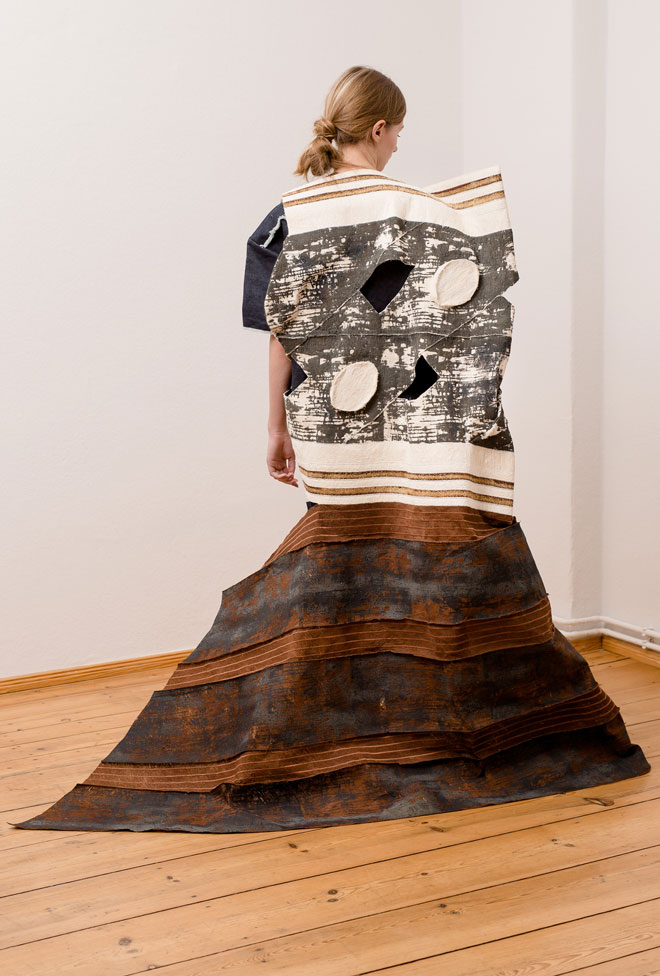 Textile art object on man consisting of a patchwork of fabrics made of sprinted and quilted bark -back view