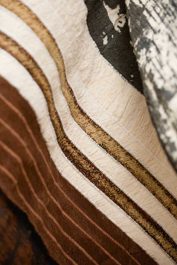 Arrangement of differently processed Bark fabrics, including a white Bark fabric with dark gray abstract print and a brown Bark fabric with quilted stripes