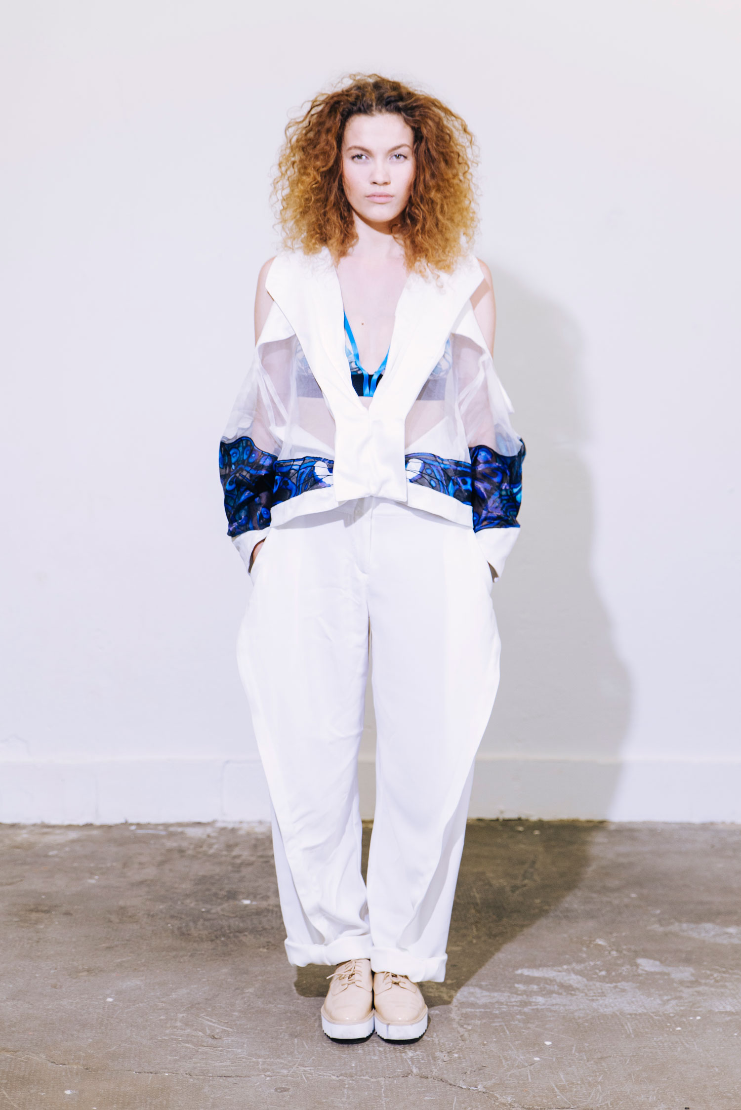 Fashion silhouette with white wide-leg trousers and blouse in suede with silk organza inserts and blue and black silk painting