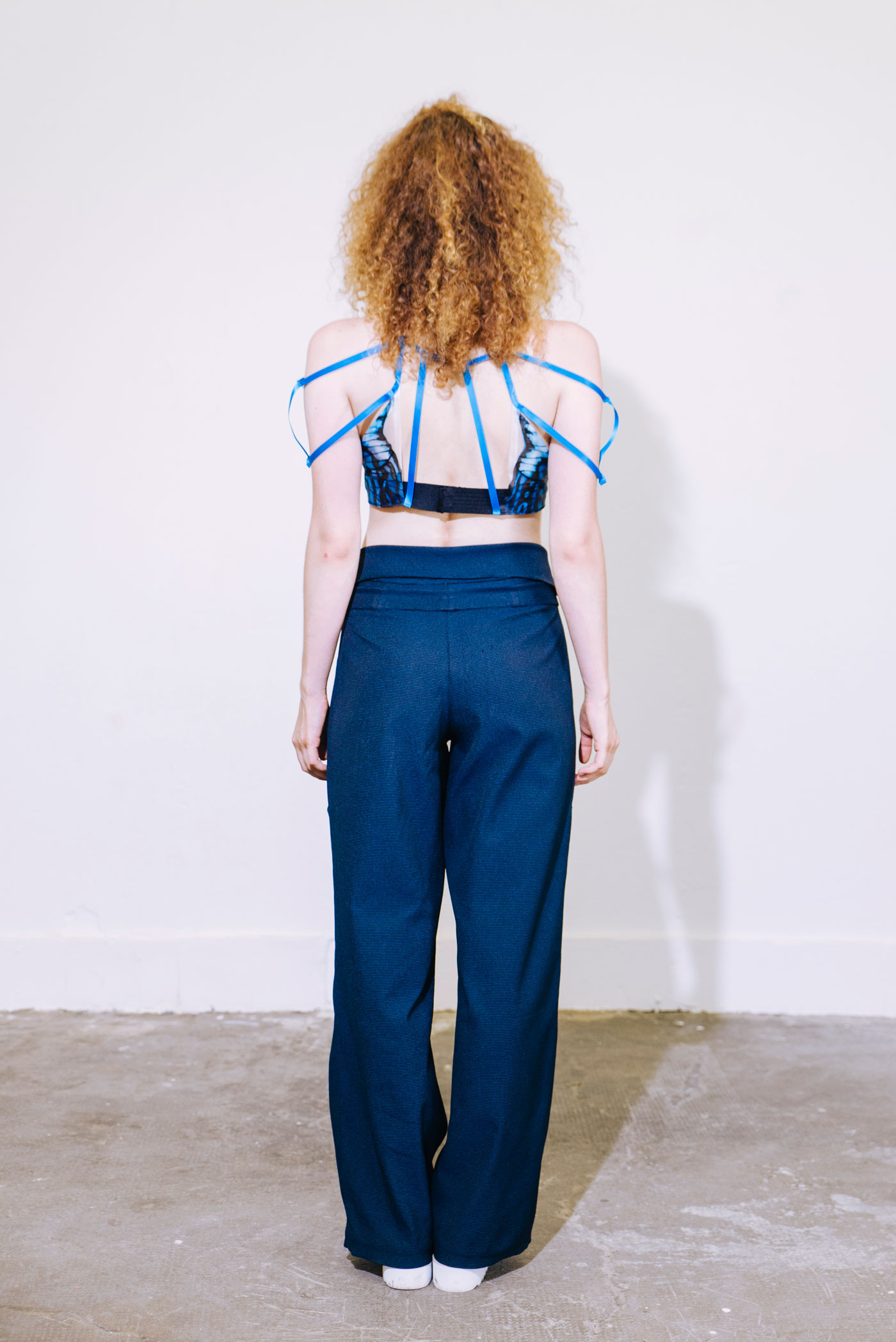Fashion silhouette with dark green trousers combined with a bustier in blue, black painted silk