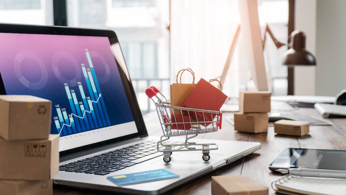 Big data and its business impacts: miniature, full shopping cart on top of a laptop with graphs on the screen