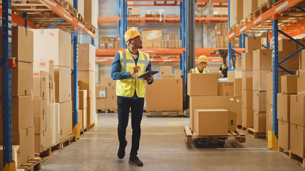 Worker wearing a hard hat walking around a warehouse