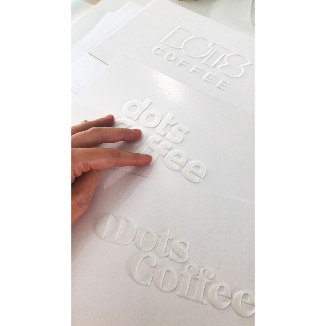 Hand touching 3d printed Dots Coffee logos