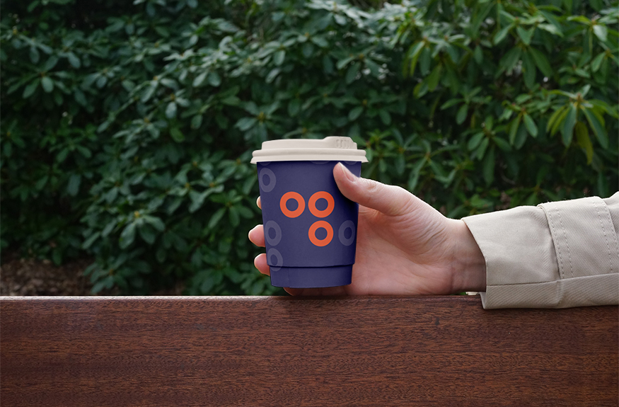 Hand holding Dots Coffee take away cup