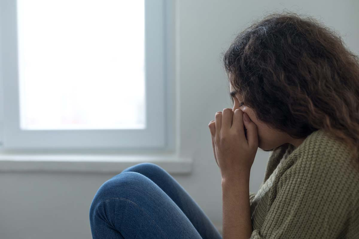 The Therapy Lounge - scared woman sitting on floor - London Hypnotherapy, NLP & CBT