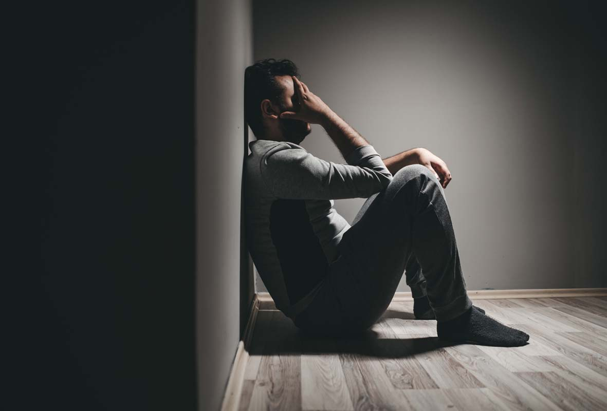 The Therapy Lounge - addiction problems man sitting on floor - London Hypnotherapy, NLP & CBT
