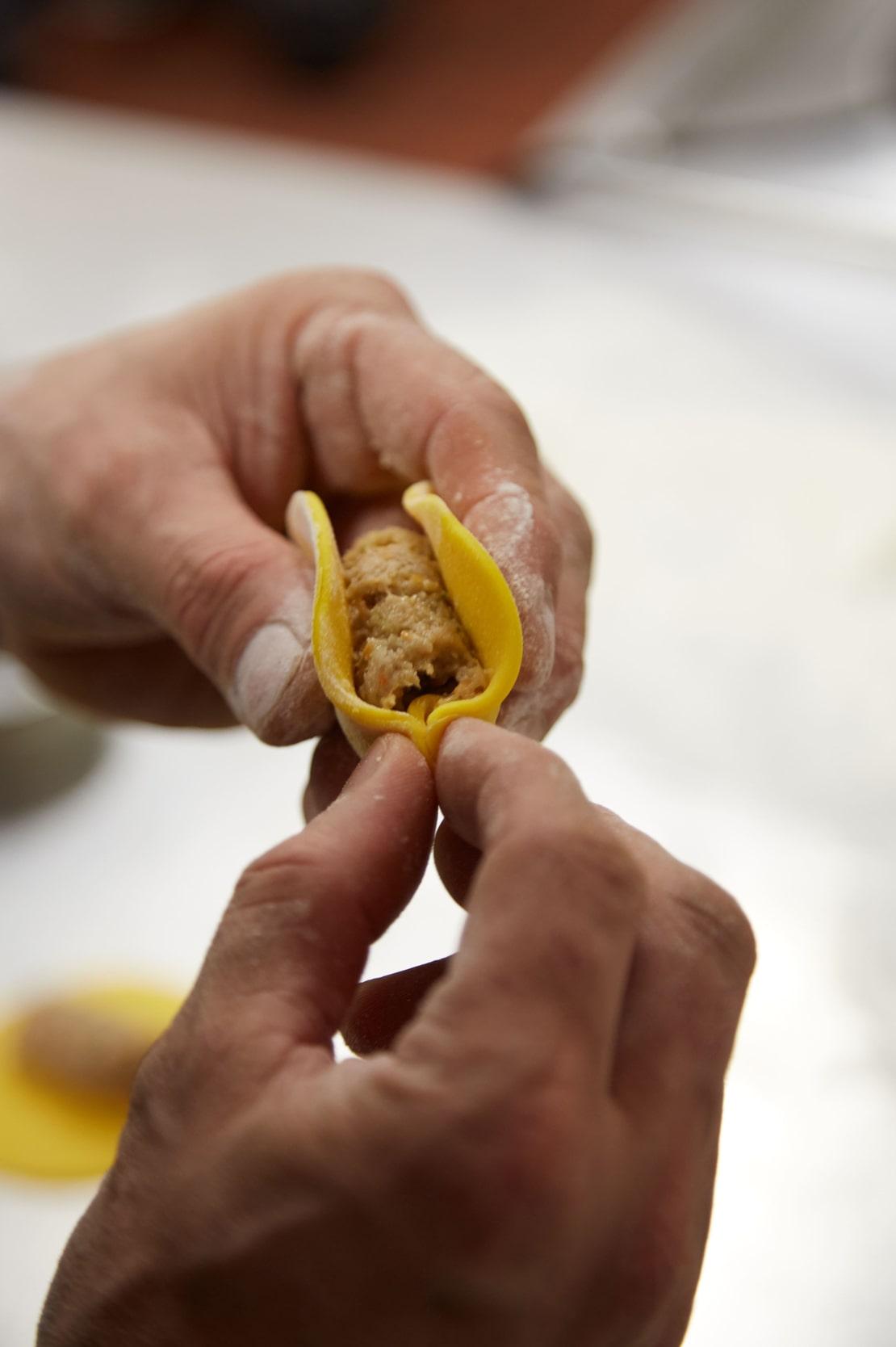 Due mani chiudono un raviolo sardo.