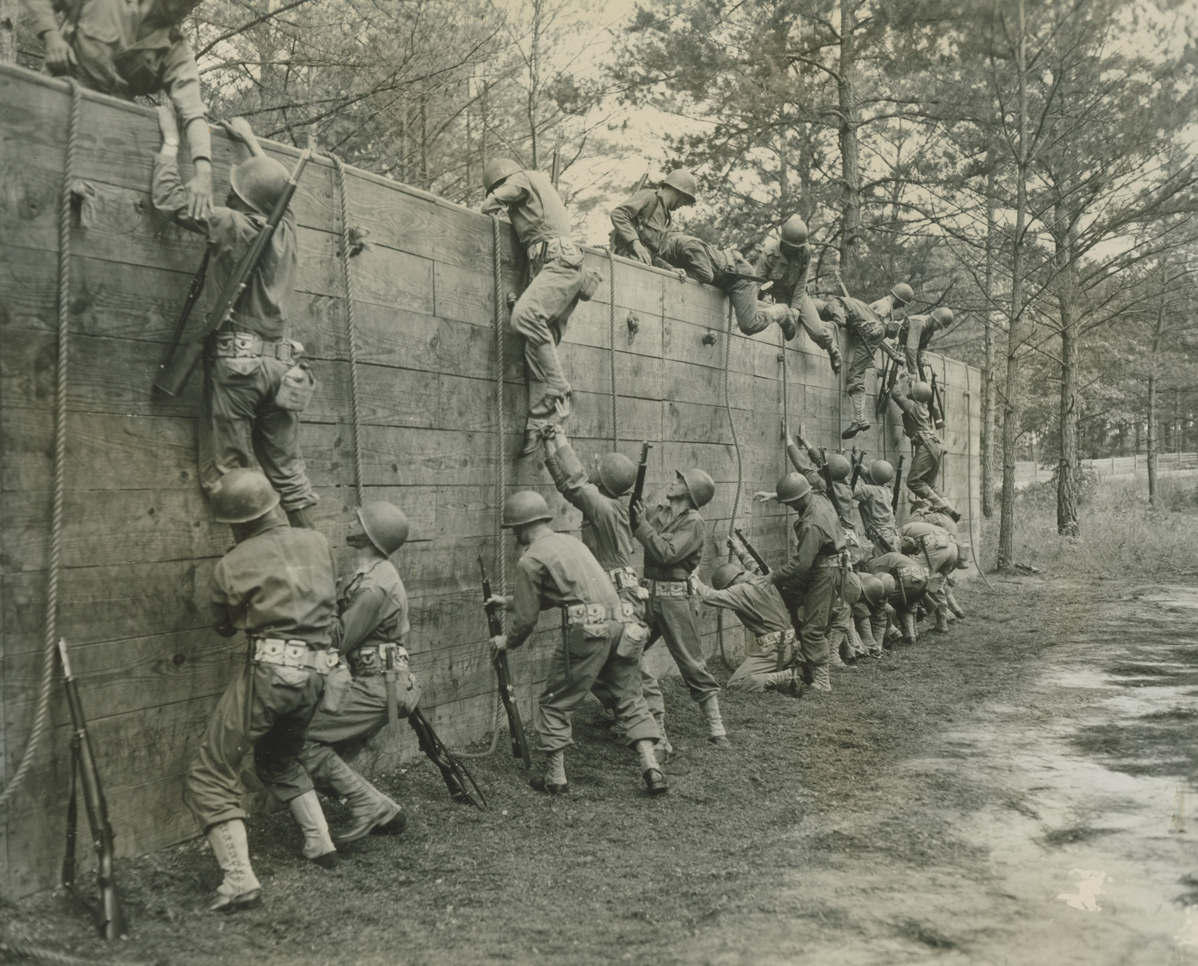 A group of infantrymen scaling an obstacle in training
