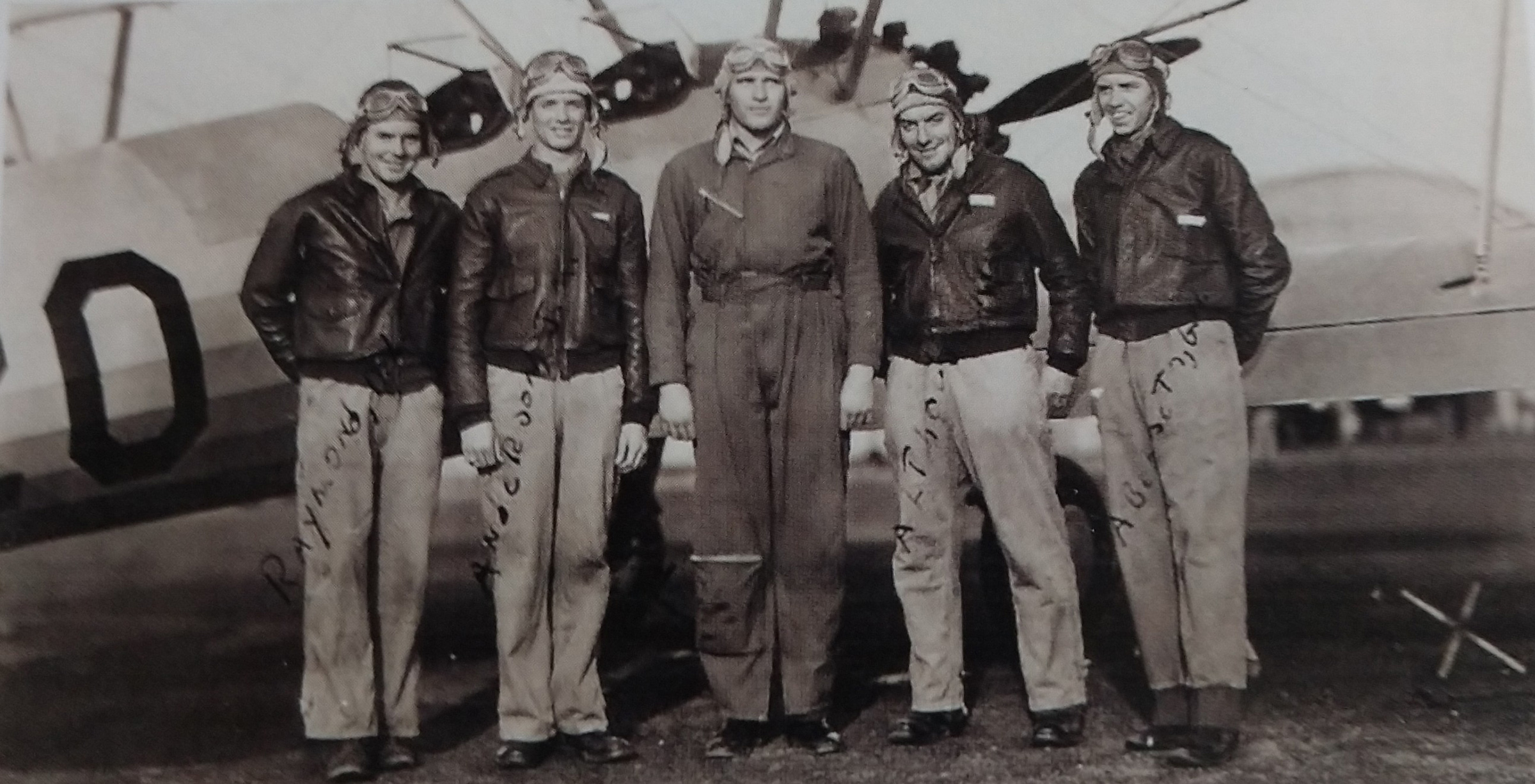 Pilots standing in front of a war plane