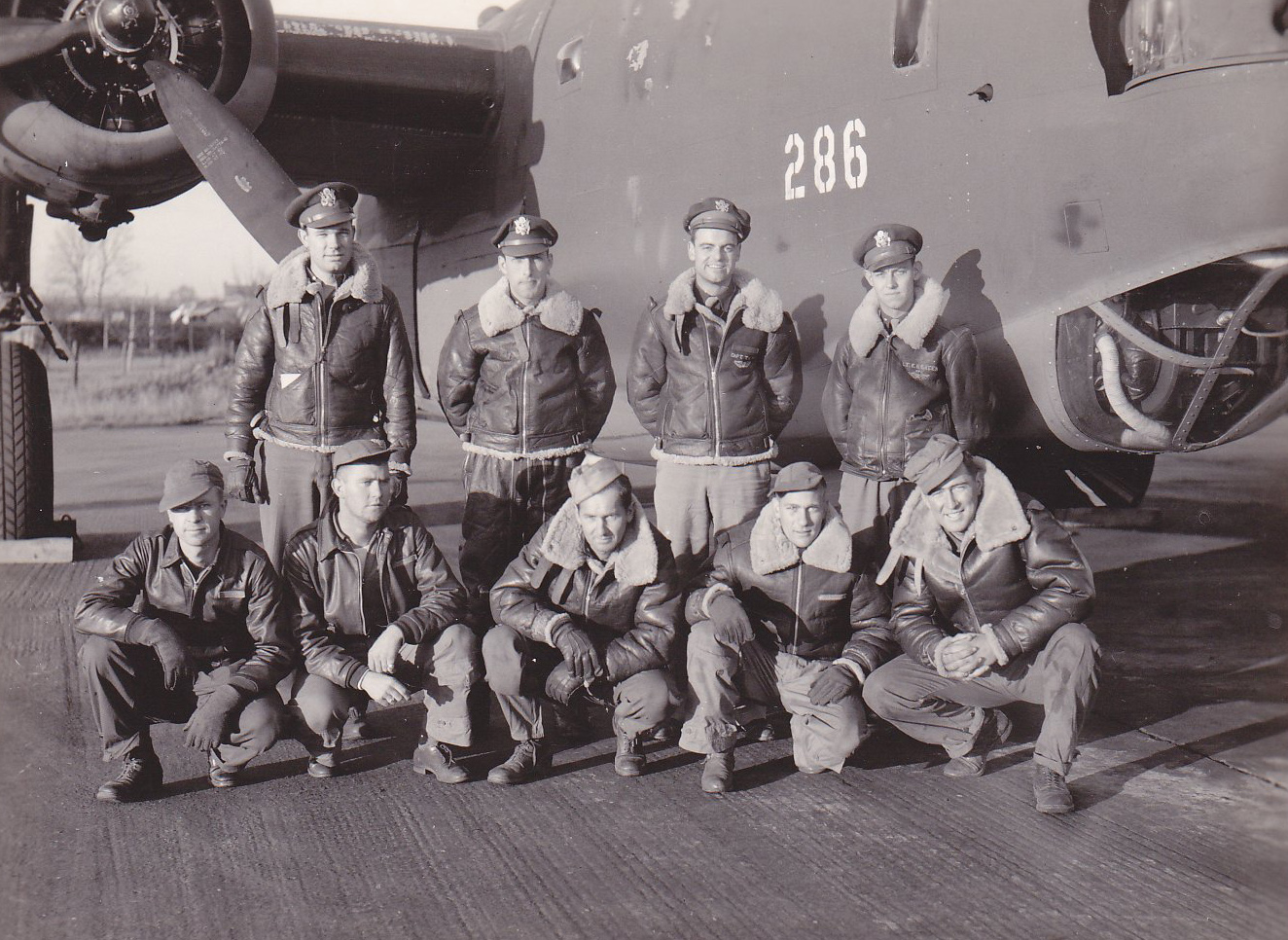Air Force pilots posing for the camera under the wing of a bomber plane