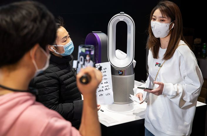 Sales associate hosting a live shopping event inside a department store in China while viewers watch and buy at home. Live shopping allows customers see-now-buy-now all in the comfort of their homes.