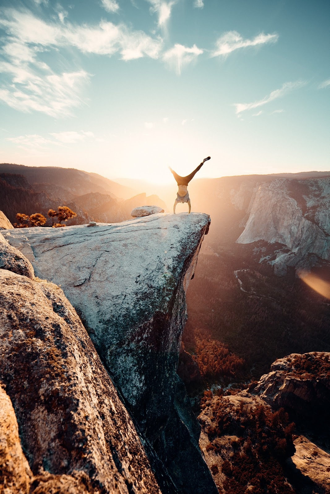 man doing handstand on the edge of a cliff with the sunset in the background