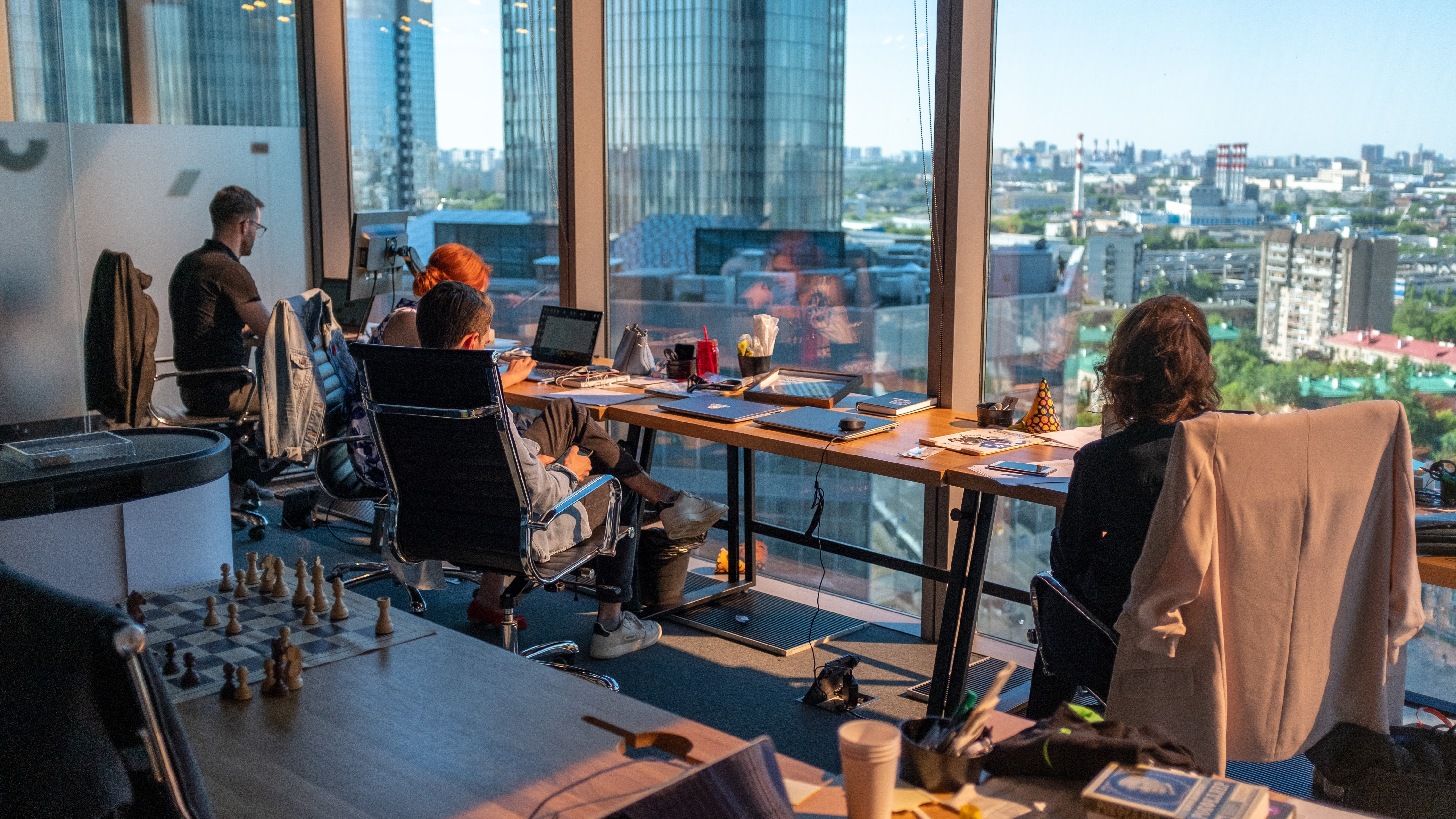 view from inside an office showing people working with large windows providing city views