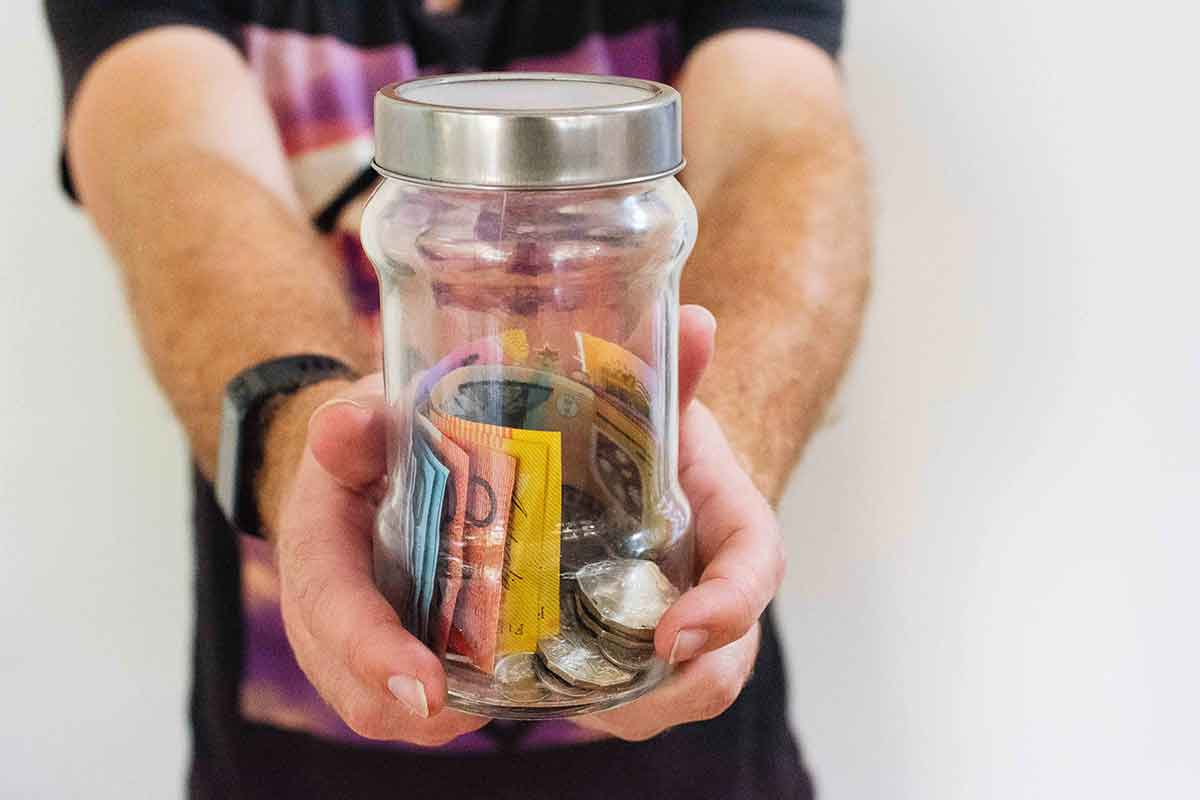 A man holding out a clear jar containing several coins and paper money.