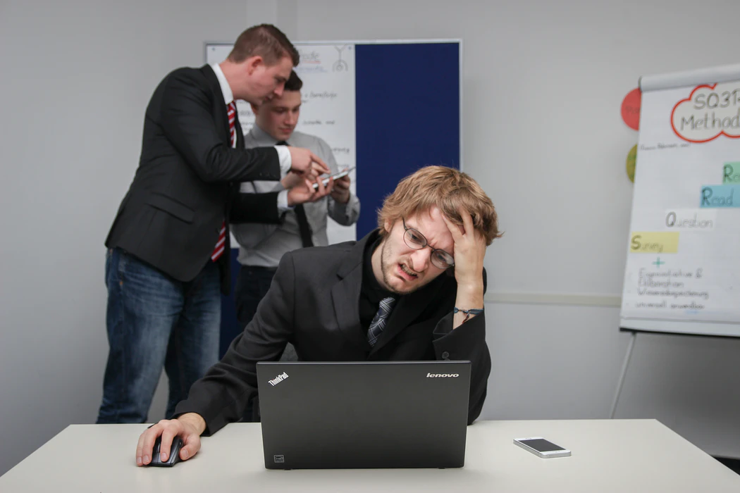 A man looking at his laptop in frustration while two people in the background are looking at a phone.