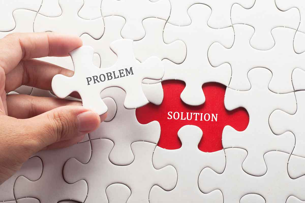 """Someone putting together a white puzzle with a hole labeled """"solution"""" and the final puzzle piece labeled """"problem."""""""